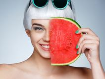 Lovely girl holding red ripe watermelon slice near her face Royalty Free Stock Photo