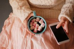 Lovely girl holding a smartphone and marshmallows in her hand. Pink marshmelow, cozy dreams of a young girl,  appetizing, tender pastel tones, photo for Stock Image