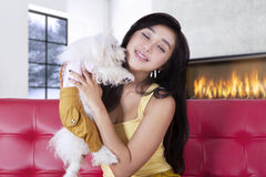 Lovely girl hugging her puppy on couch Royalty Free Stock Photo