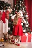 Lovely Girl In Santa Cap Near Christmas Tree, Studio Shot. Stock Photo