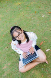 Lovely girl with a laptop on the grass Stock Photography