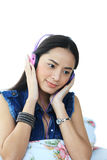 Lovely girl listening a music in headphones on white. Royalty Free Stock Photography