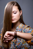 Lovely girl with long hair looks at clock Stock Photo