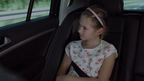 Lovely girl looking through car window during trip. Sweet elementary age girl looking through car window while sitting in the back seat of the car during road stock footage