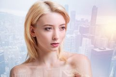 Lovely girl looking at the distance. Inborn beauty. Calm lovely girl looking at the distance while standing against beautiful modern buildings royalty free stock photography