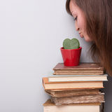 Lovely girl loving her plant and her books Stock Photos