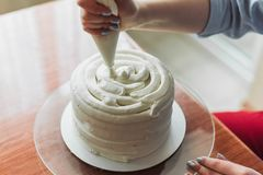 A lovely girl making a cake in a bakery. The girl smoothes the cream on the cake. White cake on a wooden table