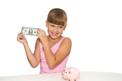 Lovely girl with money in hands isolated. Lovely little girl with money in hands and with piggy bank on table isolated Royalty Free Stock Photography