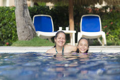 Lovely Girl and Mother Playing in Swimming Pool Royalty Free Stock Photo