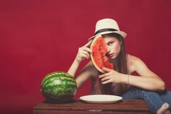 Lovely girl with pink make up, wearing jeans, hat and top, posing at red studio background near wooden box, holding slice. Watermelon, emotionally sitting royalty free stock images
