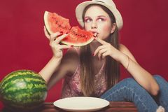 Lovely girl with pink make up, wearing jeans, hat and top, posing at red studio background near wooden box, holding slice. Watermelon, emotionally sitting stock image