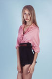 Lovely girl in a pink shirt and black shorts Stock Image