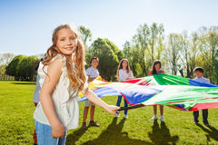 Lovely girl playing active game with friends. Portrait of lovely blonde girl waving rainbow parachute standing outdoors in a circle with her friends Royalty Free Stock Photography