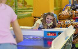Lovely girl playing air hockey game with her mum at kids amusement center