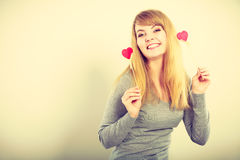 Lovely girl playing with hearts on sticks. Love and fun concept. Lovely enjoyable smiling woman playing with two little red hearts on sticks. Playful joyful Stock Image