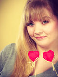 Lovely girl playing with hearts on sticks. Love and fun concept. Lovely enjoyable smiling woman playing with two little red hearts on sticks. Playful joyful Stock Images