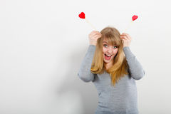 Lovely girl playing with hearts on sticks. Stock Photos