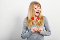 Lovely girl playing with hearts on sticks. Love and fun concept. Lovely enjoyable smiling woman playing with two little red hearts on sticks. Playful joyful Stock Photo