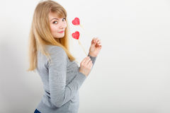 Lovely girl playing with hearts on sticks. Love and fun concept. Lovely enjoyable smiling woman playing with two little red hearts on sticks. Playful joyful Stock Photography