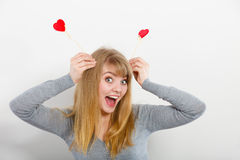 Lovely girl playing with hearts on sticks. Love and fun concept. Lovely enjoyable smiling woman playing with two little red hearts on sticks. Playful joyful Stock Photos