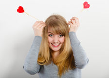 Lovely girl playing with hearts on sticks. Love and fun concept. Lovely enjoyable smiling woman playing with two little red hearts on sticks. Playful joyful Royalty Free Stock Photos