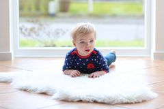 Lovely girl playing on lambskin. Lovely blonde toddler girl lying indoors at home or kindergarten on a big white soft sheepskin next to a big window with street Royalty Free Stock Photo