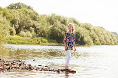 Lovely girl posing barefoot on shore of Lake Stock Images
