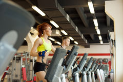 Lovely girl posing on treadmill in gym Royalty Free Stock Images