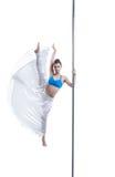 Lovely girl posing in vertical split on pole Stock Image