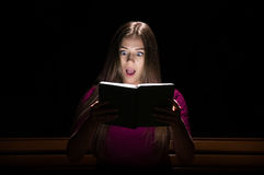 Lovely girl in a purple dress reading a book Stock Photos