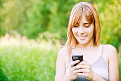Lovely girl reads sms. Lovely smiling girl reads sms on mobile phone, against green summer garden Royalty Free Stock Photography