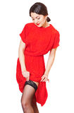 Lovely girl in red dress straightens stockings Royalty Free Stock Photo