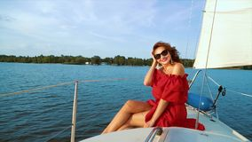 Lovely girl in red dress and sunglasses enjoying adventure on sailing boat