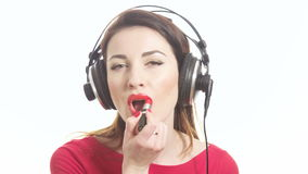 Lovely girl in red listening to the music in big headphones and dancing having fun applying red lipstick isolated on white stock video