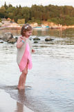 Lovely girl resting and raises dress on the beach near water Stock Images