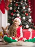 Lovely girl in santa cap lying on floor, studio shot. Stock Photography