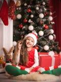 Lovely girl in santa cap lying on floor, studio shot. Royalty Free Stock Photo