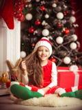 Lovely girl in santa cap lying on floor, studio shot. Stock Photos
