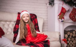 Lovely girl in santa cap lying on a sofa, studio shot. Royalty Free Stock Photo