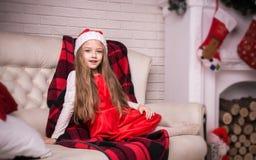 Lovely girl in santa cap lying on a sofa, studio shot. Stock Photo