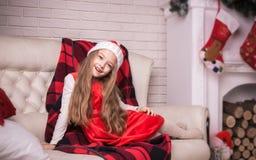 Lovely girl in santa cap lying on a sofa, studio shot. Royalty Free Stock Photos