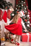 Lovely girl in santa cap near christmas tree, studio shot. Stock Photo