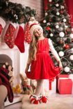 Lovely girl in santa cap near christmas tree, studio shot. Royalty Free Stock Photos