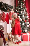 Lovely girl in santa cap near christmas tree, studio shot. Stock Image