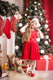 Lovely girl in santa cap near christmas tree, studio shot. Royalty Free Stock Images