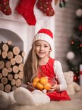 Lovely girl in santa cap with tangerines in hand, studio shot. Royalty Free Stock Photos