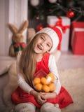 Lovely girl in santa cap with tangerines in hand, studio shot. Stock Images