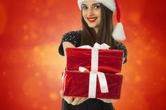 Lovely girl in santa hat with red gift. Box in hands smiling on red background Royalty Free Stock Photography