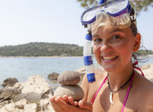 Lovely girl at the seaside wearing a diving mask and holding sea urchins Stock Photo
