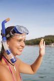 Lovely girl at the seaside wearing a diving mask and waving hello Royalty Free Stock Image